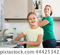 girl and mom tidy kitchen up 44425342