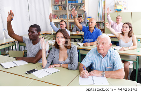 Group different ages asks questions during exam 44426143