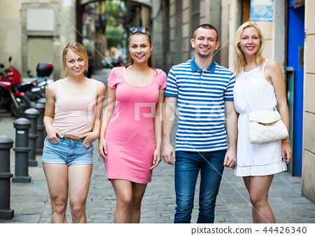 Four smiling persons walking together 44426340