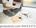 Woman reading book or newspaper and drinking coffee breakfast on 44432373