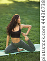 Woman practicing yoga outdoors in park 44436738