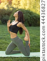 Woman practicing yoga outdoors in park 44436827