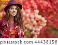 Beautiful woman in autumn park 44438156