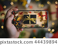 Hand Taking Picture of Black Gold Christmas 44439894