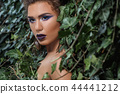 Girl with professional make up, seductive looking at side wrapping in green ivy. 44441212