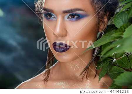 Seductive girl with bright colored makeup and peacock feathers earrings, looking at side. 44441218