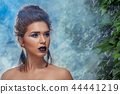 Hot girl with perfect make up posing in blue smoke against green herb. 44441219