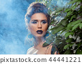 Girl with dark purple lips, bright eyes and earrings made of peacock feathers. 44441221
