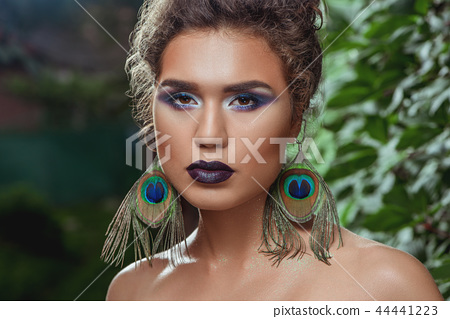 Close up of girl with make up posing against green bushes. 44441223