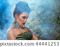 Extraordinary woman standing with lowered head, wearing in big peacock earrings. 44441253