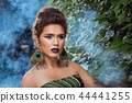 Woman with make up posing against green bush in blue smoke. 44441255