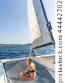 Woman relaxing on a summer sailing cruise, sitting on a luxury catamaran near picture perfect Palau 44442702