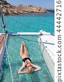 Woman relaxing on a summer sailing cruise,lying in hammock of luxury catamaran near picture perfect 44442716