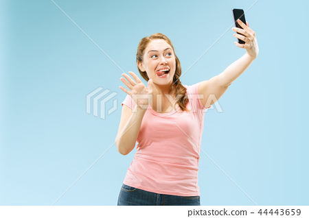 Portrait of a happy smiling casual girl showing blank screen mobile phone isolated over blue 44443659