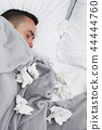 ill man in bed surrounded by used tissues 44444760