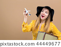Young woman with a suitcase and toy airplane travel theme 44449677