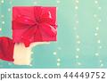 Santa holding a Christmas gift 44449752
