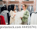 Beautiful girls are choosing clothes, talking and smiling while doing shopping in boutique 44450741