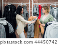 Sales consultant helping chooses clothes for the customer in the store. Shopping with stylist 44450742