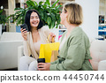 Happy young fashionable women taking a coffee break after shopping, smiling with a coffee-to-go in 44450744
