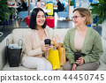 Portrait of smiling women with shopping bags and coffee to go looking at camera at the shopping mall 44450745