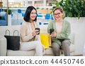 Two young women having coffee break together at shopping mall 44450746
