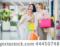 Laughing girls carrying bags with purchases in shopping mall 44450748