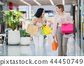 Two happy young women walking in shopping mall with shopping bags 44450749
