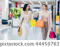 Shopping women talking happy holding shopping bags having fun laughing. Two beautiful young woman 44450763