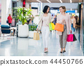 Two happy friends girls with shopping bags walking in mall 44450766