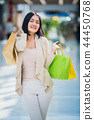 A dark-haired woman wearing muted, gentle colours holds colourful, patterned shopping bags walks at 44450768