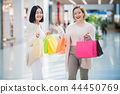 Two happy friends girls with shopping bags walking in mall 44450769