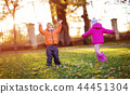 children throwing leaves in beautiful autumnal day 44451304