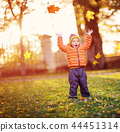 Child standing with umbrella in beautiful autumnal day 44451314