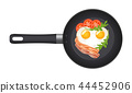 Pan with fried egg in the shape of a heart, with bacon, tomatoes and arugula. Top view. Creative 44452906