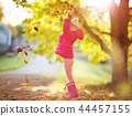 Child standing with umbrella in beautiful autumnal day 44457155