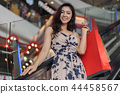 happy woman with shopping bags on escalator in mall 44458567