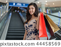 happy woman with shopping bags on escalator in mall 44458569