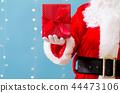 Santa holding a Christmas gift 44473106