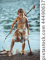Angry caveman, manly boy with primitive weapon hunting outdoors. Ancient prehistoric warrior. Heroic 44490637