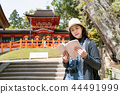 tourist reading information on her guidebook 44491999