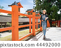 tourist walking in temple and holding guidebook 44492000