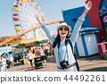 joyful female traveler raising arms to the sky 44492261