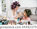 lovely mom help her kid doing makeup 44492379
