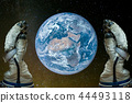 Man in astronaut gloves holding the planet Earth 44493118