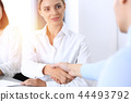 Business handshake by blonde woman and her partner at meeting. Concept of success and agreement 44493792