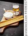 golden beer and delicious salty snacks on an old black wooden table 44496357