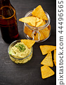 beer and a bowl of guacamole with nachos on an old black wooden table 44496565