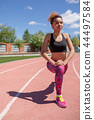 Young fitness woman runner warm up before running on track. 44497584