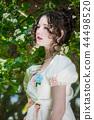 woman in an long white bride dress in flowers tree 44498520